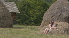 Brunette girl drinking fresh milk on meadow in the village Stock Footage