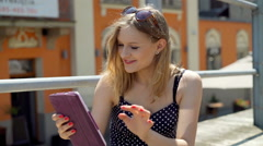 Girl browsing internet on tablet and smiling to the camera in the city Stock Footage