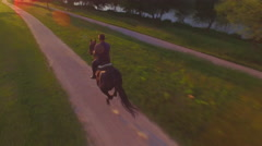 AERIAL: Senior cowboy horseback riding dark brown horse in nature at sunset Stock Footage