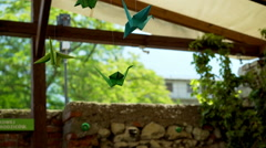 View of the green, origiami birds hanging on the cafe's roof Stock Footage