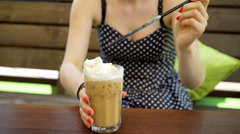 Girl eating whipped cream by using a straw from frappe Stock Footage