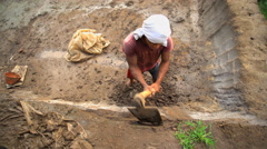 Male manually digging out soil material to make handmade bricks Java Stock Footage