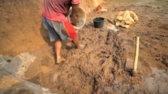Male mixing soil material to make handmade bricks Java Indonesia Stock Footage