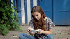 Pretty girl sitting on the ground and playing a game on tablet Stock Footage