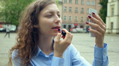 Pretty girl using smartphone as a mirror while painting her lips Stock Footage
