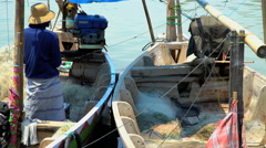 Indonesian male local fishermen tending colorful boats Java South East Asia Stock Footage