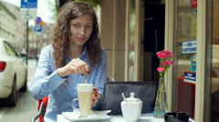 Pretty girl mixing latte in the outdoor cafe and smiling to the camera Stock Footage