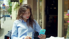 Pretty girl texting on smartphone in the cafe and drinking latte Stock Footage