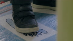 Close up view of boy's feet in black sneakers Stock Footage