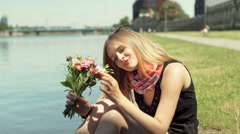 Pretty girl holding bunch of flowers and smiling to the camera by the river Stock Footage