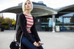 Bored Woman With Mobile Phone Sitting On Luggage Outside Station Stock Photos