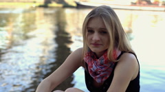 Unhappy girl sitting by the river and looking to the camera Stock Footage