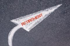 Directional white painted arrow with word RETIREMENT over road surface Stock Photos