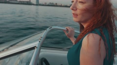 Red hair girl in turquoise dress drive motor boat. Summer evening. Romantic Stock Footage