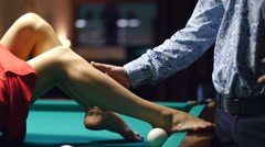 Man gently stroked the girl her legs - on a billiard table Stock Footage