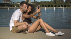 Romantic couple making photos by the lake in summer park. Stock Footage