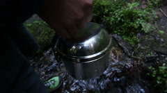 Filling pot of water from mountain river. Camping saucepan Stock Footage