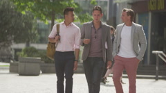 4K Happy casual male friends chatting as they walk through the city Stock Footage