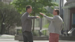 4K Happy casual male friends high five as they walk through the city Stock Footage