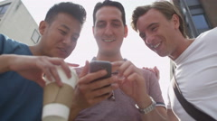 4K Happy casual male friends using wireless technology the city Stock Footage