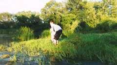 Close aerial shot of two Kids playing at a river in wild nature Stock Footage