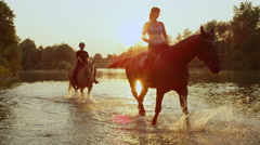 CLOSE UP: Young girls riding horses by the riverbank at golden sunrise Stock Footage