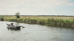 The guy in the boat floating on the narrow river. Slowmotion Stock Footage