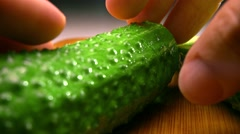 Man's hands splitting green cucumbers on wooden cutting board. 4K close up shot Stock Footage