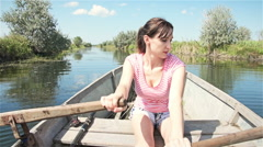 Attractive woman rowing oars in a wooden boat Stock Footage