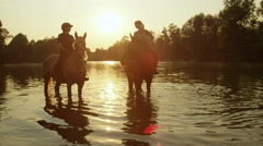 CLOSE UP: Two horses standing in shallow river with riders at golden sunrise Stock Footage