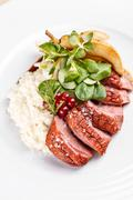 Roast goose breast on white plate, fine dining Stock Photos