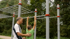 Dad teaches his son to do pull-ups, on the sportground Stock Footage