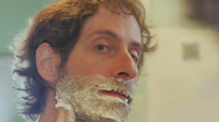 A man with a full beard applies shaving cream to his face - handheld Stock Footage