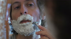 A man uses a safety razor to shave his beard - handheld Stock Footage