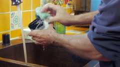 A man washing a cup with a sponge with a fast shutter speed - dolly Stock Footage