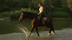 SLOW MOTION: Young cheerful girl rider horseback riding in shallow river Stock Footage