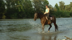 SLOW MOTION: Young happy girl rider horseback riding in shallow river Stock Footage