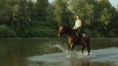 SLOW MOTION: Young smiling girl rider horseback riding in shallow river Stock Footage