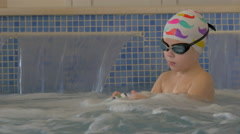 Child getting hydromassage in pool Stock Footage