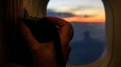 Closeup Man Photos Sunset Clouds out of Dark Liner Window Stock Footage