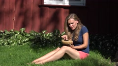 Happy woman in shorts sitting near rural wooden house eating blackberry black Stock Footage