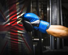 Brexit, blue gloves with yellow europe stars punching into a British bag Stock Photos
