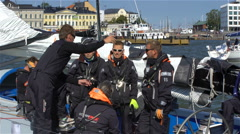 The Crew of a sailboat discusses race strategy before the start of the regata. Stock Footage