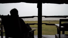A man in silhouette from the back watching the rain from a hut in Mali, Africa. Stock Footage