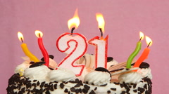Happy 21 birthday cake and candles on a pink background Stock Footage