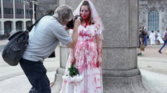 Bloodied zombie bride posing for pictures in public square Stock Footage