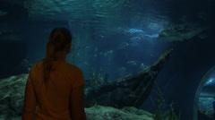 Woman looking at shark at the big aquarium. Siam Ocean World, Bangkok, Thailand Stock Footage