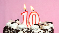 Celebration anniversary 10 years with cake and candles on pink background Stock Footage