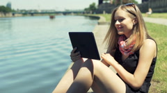 Happy girl recall memories while browsing photos on tablet by the river Stock Footage