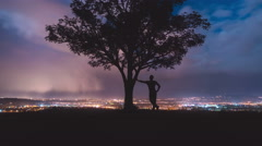 The man lean on the tree against the background of night city. Time lapse Stock Footage